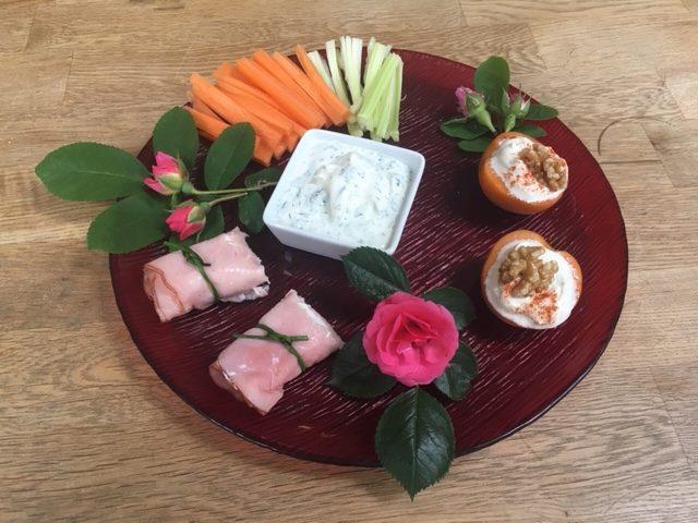 Teller mit Schinken-Käse-Röllchen, Marillen-Käse-Happen, Karotten- und Selleriesticks mit Dip; geschmückt mit Rosenblüten und -blättern