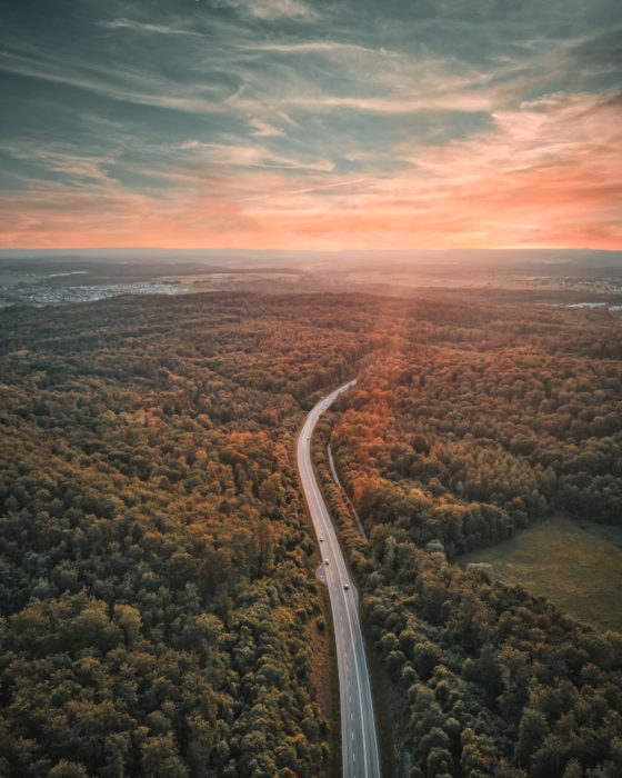 Luftbild einer Straße durch Wald, im Hintergrund der Horizont in der Abenddämmerung