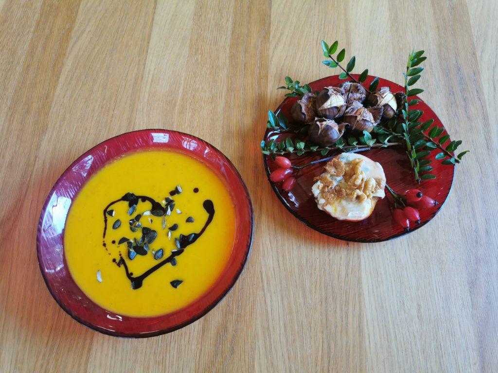 2 rote Teller, einer mit Kürbiscremesuppe mit gehackten Kürbiskernen und Kernöl, einer mit Maroni und einem gebratenen Apfel mit Gorgonzola und Walnüssen