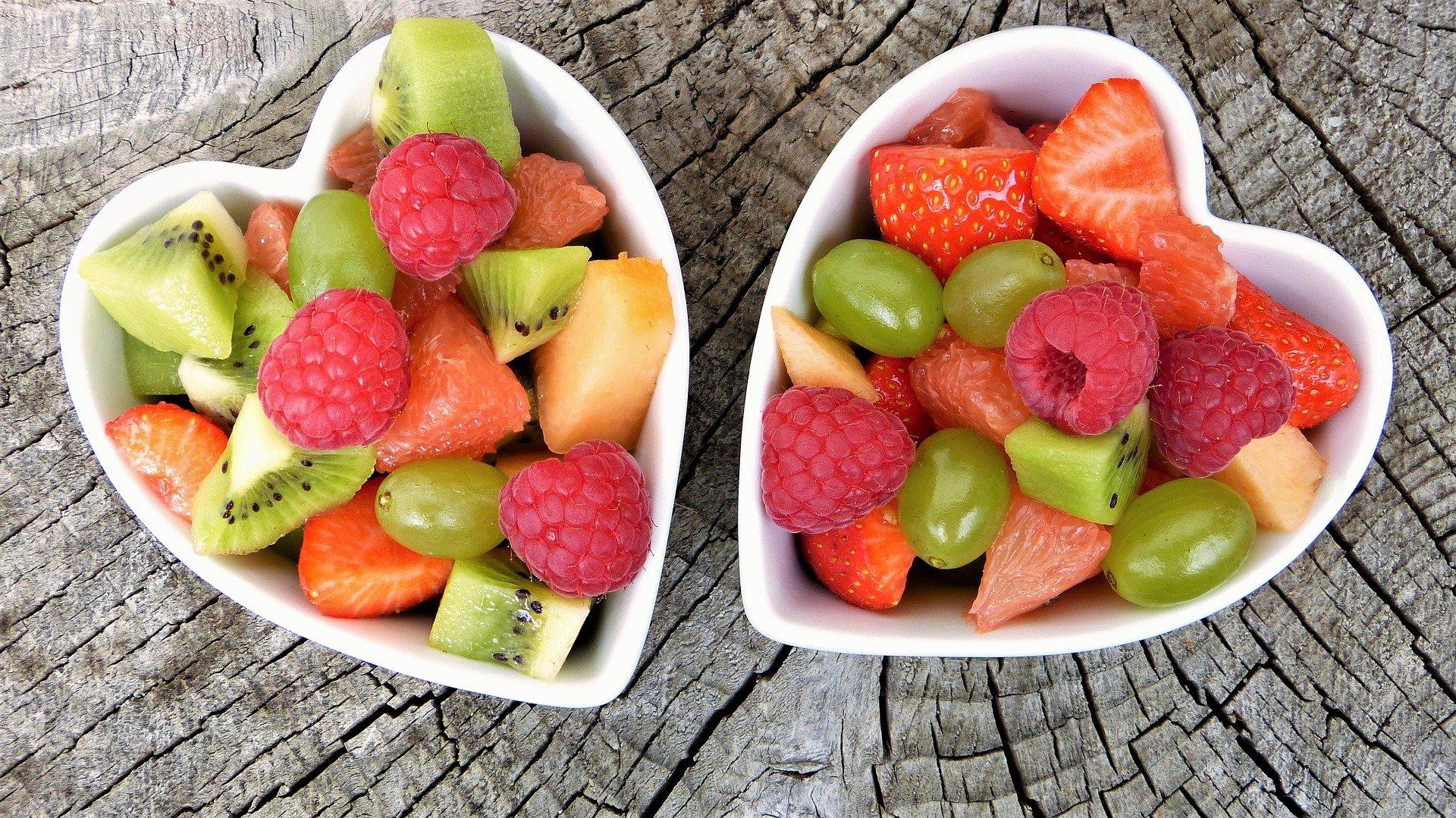 gemischtes Obst in zwei herzförmigen Schüsseln angerichtet, auf einem Baumstamm platziert