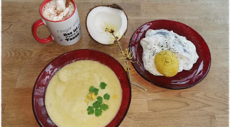 Mais-Kokossuppe, Matjessalat, heiße Schokolade - arrangiert auf einem Holztisch mit einer halben Kokosnuss und einem Zaubernuss-Zweig als Deko