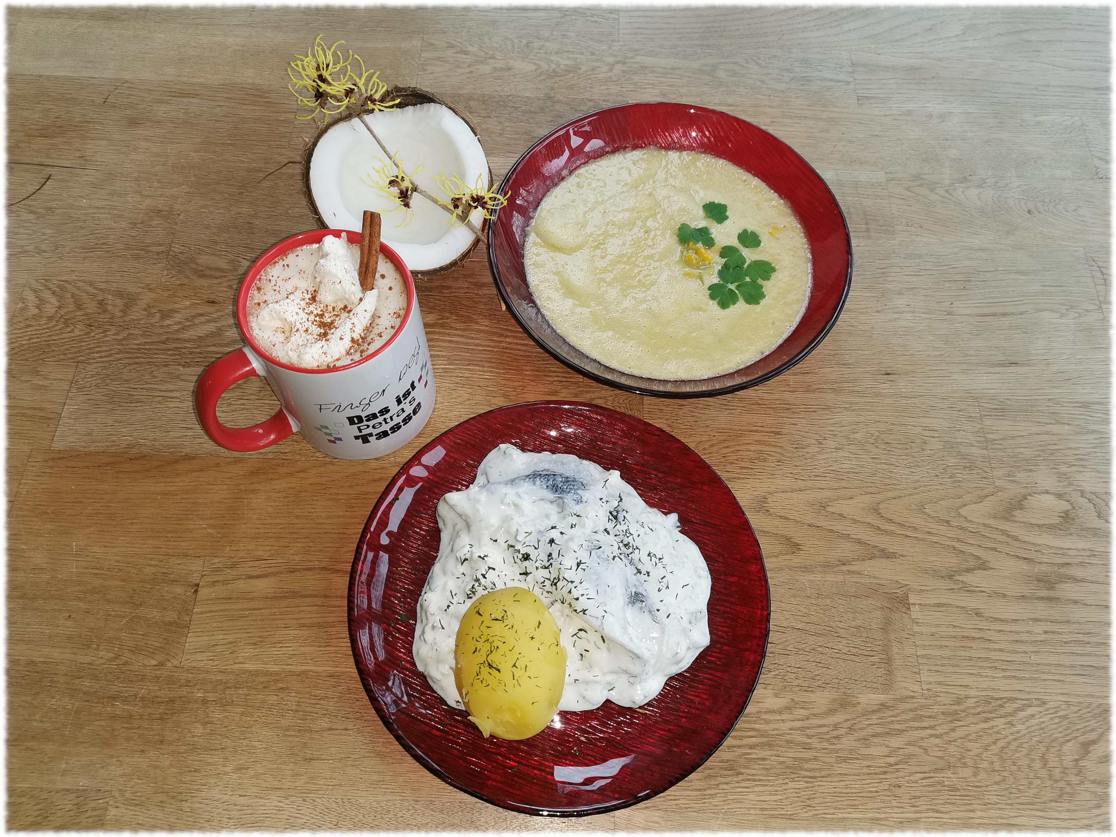 Matjessalat, Mais-Kokossuppe, heiße Schokolade - arrangiert auf einem Holztisch mit einer halben Kokosnuss und einem Zaubernuss-Zweig als Deko