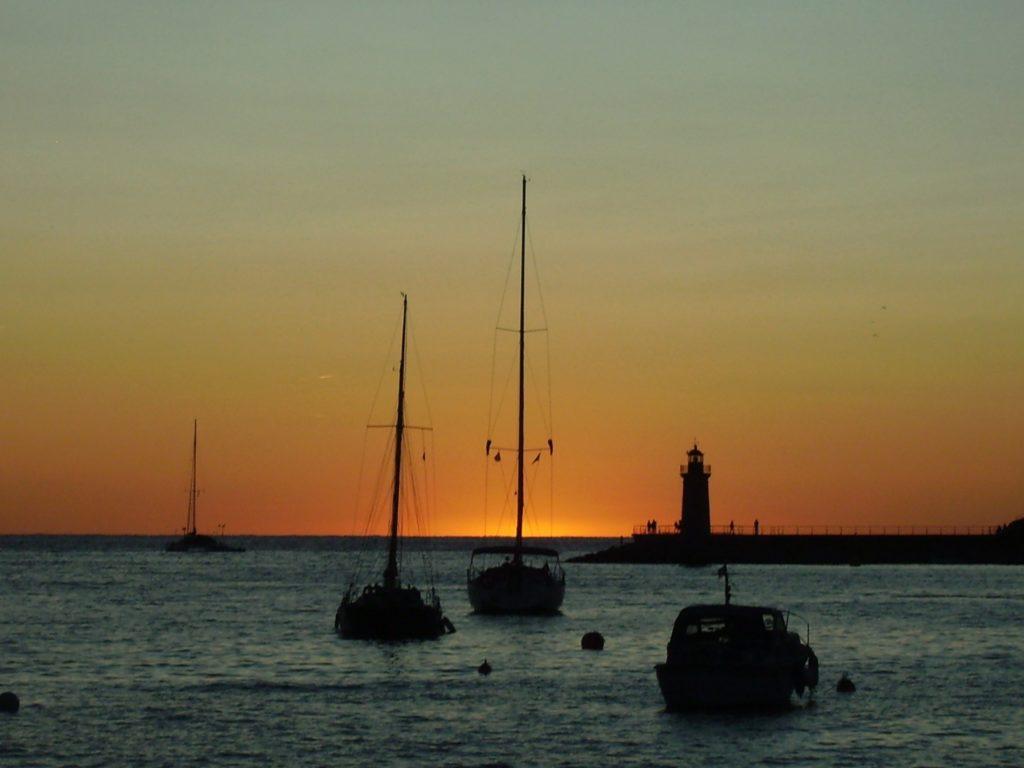 3 Segelboote liegen in der Abendstimmung im Hafen; am Horizont, hinter einem Leuchtturm, verschwindet die orange-gelbe Sonne im Meer
